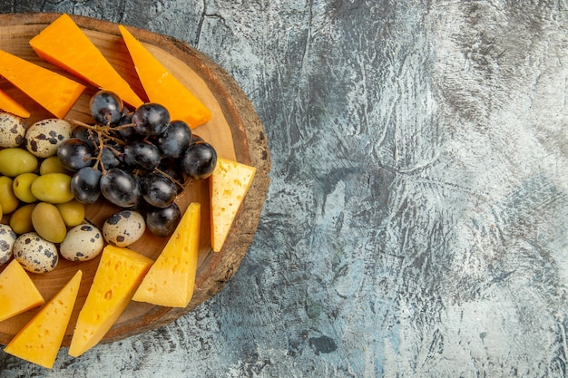Halber schuss köstlicher snacks mit obst und speisen für wein auf einem braunen tablett auf grauem hintergrund in horizontaler ansicht