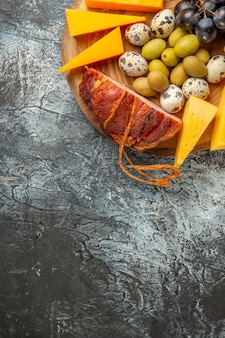 Halber schuss köstlicher snacks mit obst und speisen für wein auf einem braunen tablett auf grauem hintergrund