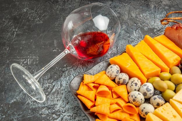 Halber schuss leckeren besten snacks auf einem braunen tablett und gefallenem weinglas auf grauem hintergrund