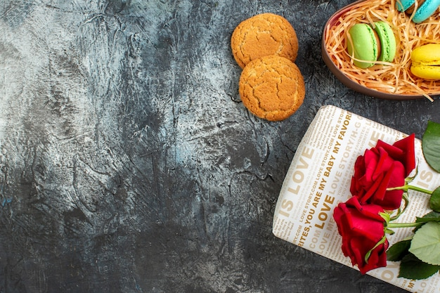 Halber schuss roter rose auf schöner geschenkbox mit leckeren macarons und keksen auf eisigem dunklem hintergrund