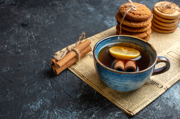 Halber schuss teezeit mit gestapelten leckeren keksen zimt zitrone auf einer alten zeitung auf dunklem hintergrund