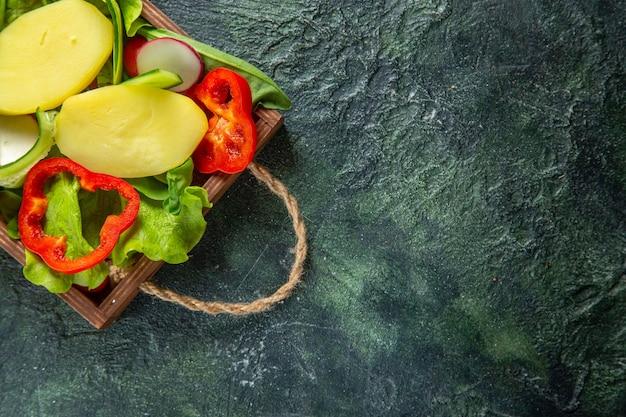 Halber schuss von frisch gehacktem gemüse auf einem holztablett auf der rechten seite auf mischfarbenoberfläche mit freiem platz