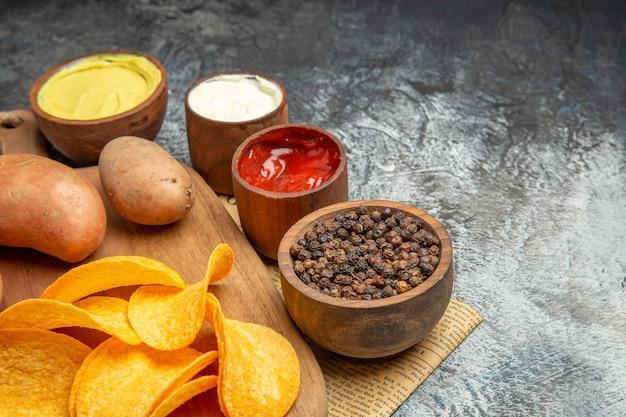 Halber schuss von hausgemachten köstlichen kartoffelchips auf holzschneidebrett verschiedene gewürze und aromen auf zeitung auf grauem tisch