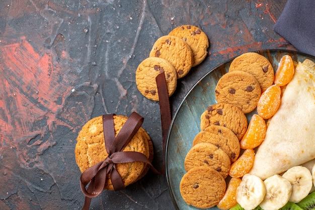 Halber schuss von köstlichen crepe-gehackten zitrusfruchtkeksen auf dunklem handtuch auf gemischter farbe