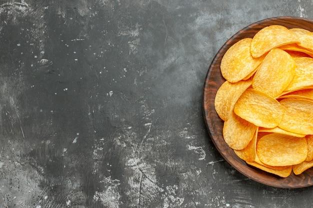 Halber schuss von köstlichen hausgemachten kartoffelchips auf einem braunen teller auf grauem tisch