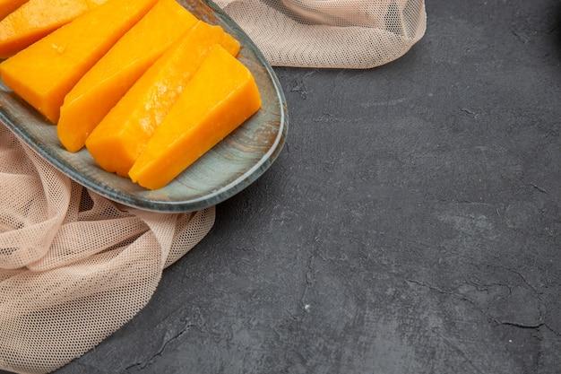 Halber schuss von natürlichem frischen gelben käse auf einem halb gefalteten handtuch auf schwarzem hintergrund black