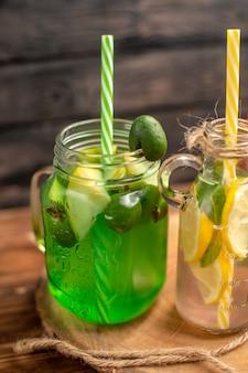 Halber schuss von natürlichen bio-früchtensäften in flaschen, serviert mit röhren auf einem holzbrett auf einem braunen tisch served