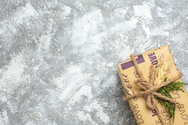 Halber schuss von schönem weihnachtsgeschenk mit liebesinschrift auf eisoberfläche