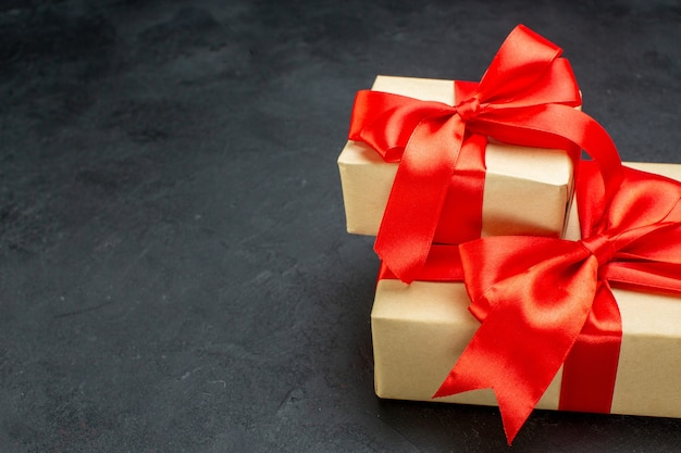 Halber schuss von schönen geschenken mit rotem band auf dunklem hintergrund in horizontaler ansicht