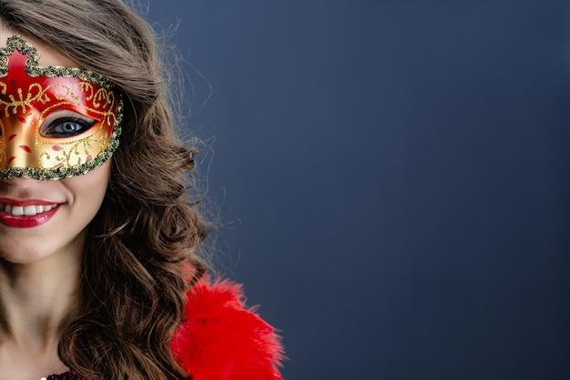 Halbes gesicht der lächelnden tragenden karnevalsmaske der frau über blauem hintergrund