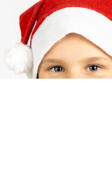 Halbes gesicht des kindes in weihnachtsmann-hut ist hinter weißer leerer karte isoliert auf weißem hintergrund mit c...