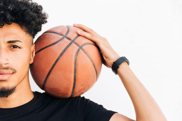 Halbes gesicht des schwarzen mannes mit basketball