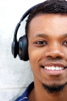 Halbes portrait des lächelnden mannes mit kopfhörern hörend musik