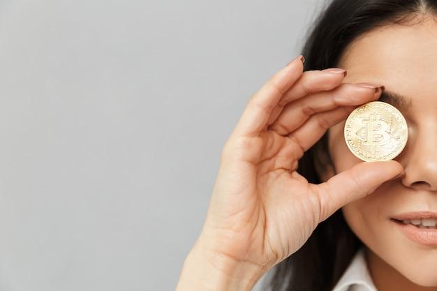 Halbes seitenfoto der reichen frau mit langen braunen haaren, die ihre augen mit goldenem bitcoin bedecken, lokalisiert über graue wand