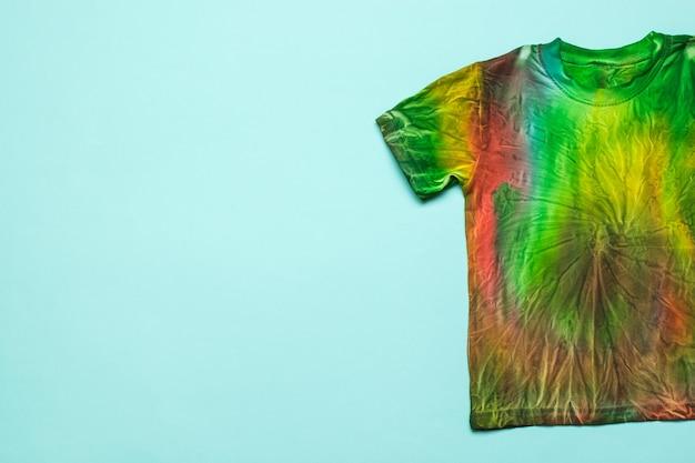 Halbes t-shirt im tie-dye-stil auf hellblauem grund. platz für den text. kleidung zu hause von hand färben. flach liegen.