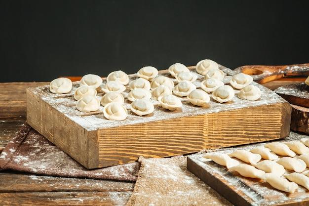 Halbfertige russische knödel pelmeni auf dem holzbrett mit mehl
