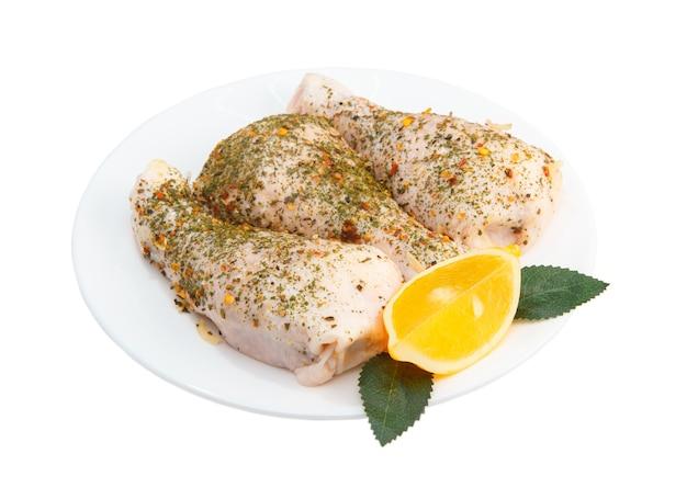 Halbfertiges geflügelfleisch. gefüllte hähnchenschenkel auf einem weißen teller isoliert. nahrungsprotein. huhn und gewürze. rezepte aus den beinen. rohe lebensmittel.