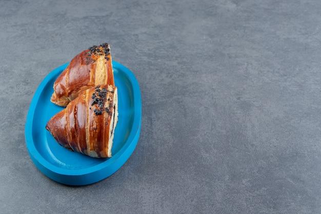 Halbgeschnittene leckere croissants mit schokolade auf blauem teller.