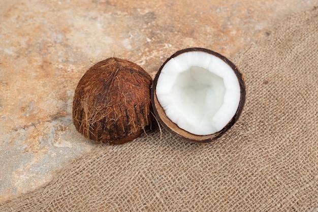 Halbgeschnittene reife kokosnüsse auf marmoroberfläche mit sackleinen.