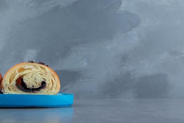 Halbgeschnittenes leckeres croissant mit schokolade auf blauem teller.