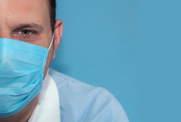 Halbgesichtsdetail der männlichen krankenschwester der grünen augen mit wegwerfbarer gesichtsmaske und blauem hintergrund
