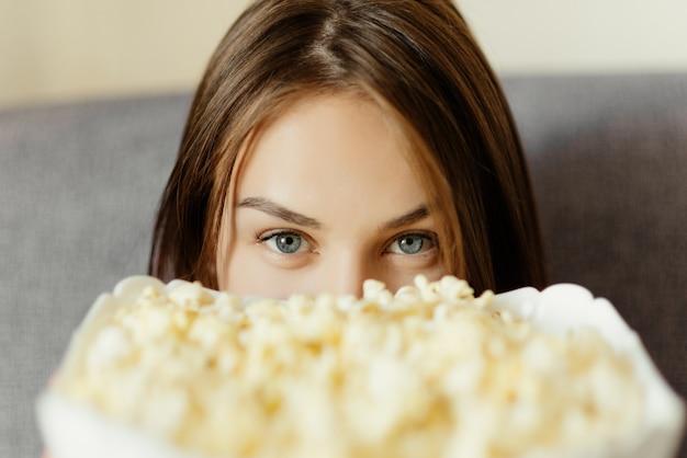 Halbgesichtsfoto einer jungen frau mit einer schüssel popcorn. nahansicht.