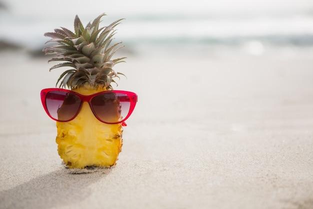 Halbierte ananas und eine sonnenbrille auf dem sand gehalten