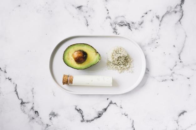 Halbierte avocado; geriebener körperpeeling und reagenzglas auf weißem tablett gegen marmorstrukturhintergrund