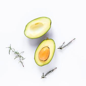 Halbierte avocado und kräuter gegen weißen hintergrund