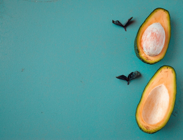 Halbierte avocados auf hölzernem hintergrund