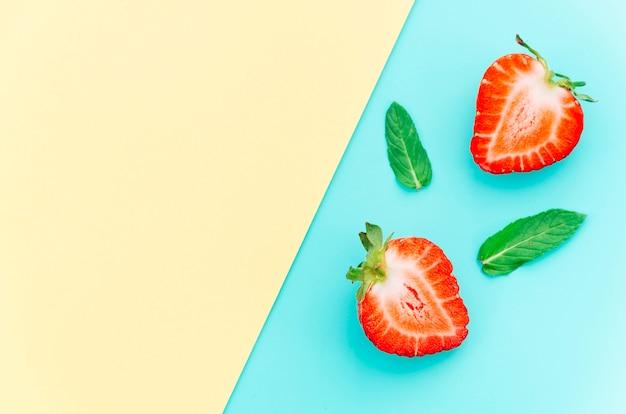 Halbierte leckere reife erdbeeren und grüne blätter