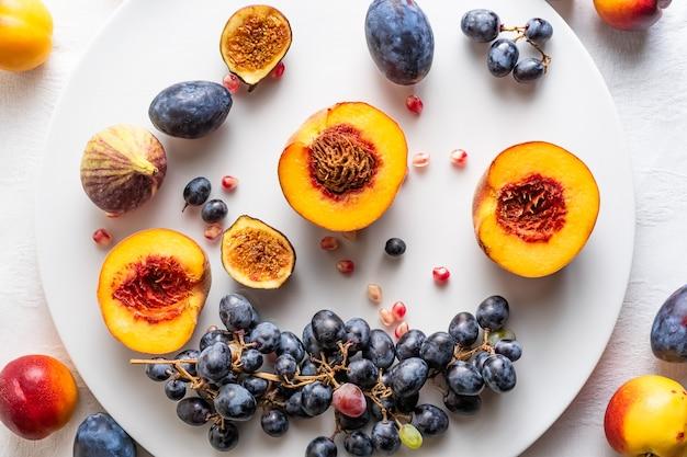 Halbierte pfirsiche mit nektarinen und trauben auf weißer platte