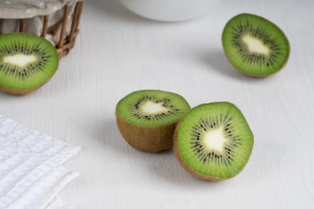 Halbierte reife grüne kiwi-fruchtscheiben serviert auf weißem holztisch mit handtuch