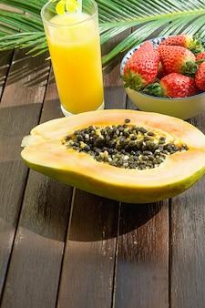Halbierte reife papaya-frische erdbeeren im schüsselananassaft