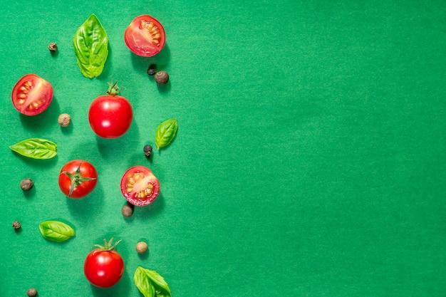 Halbierte saftige kirschtomaten und basilikumblätter. konzept für eine gesunde ernährung. draufsicht. speicherplatz kopieren.