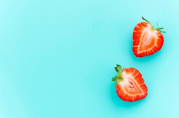 Halbierte saftige reife erdbeeren mit grünen stielen