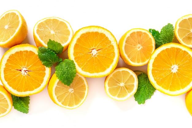 Halbierte zitronen und orangen liegen in einer reihe, draufsicht. zitrusfrüchte und minzblätter für die herstellung von limonade, kopierraum.