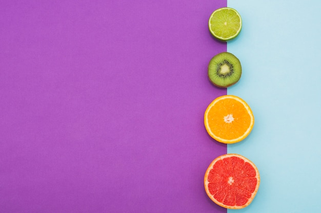 Halbierte zitrusfrüchte; kiwi an der grenze des doppelten hintergrundes