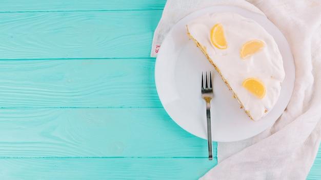 Halbierter gebackener zitronenkuchen mit käseaufstrich und scheiben von zitrusfrüchten auf platte