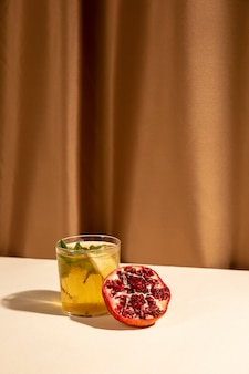 Halbierter granatapfel mit köstlichem cocktailgetränk vereinbarte auf schreibtisch gegen braunen vorhang
