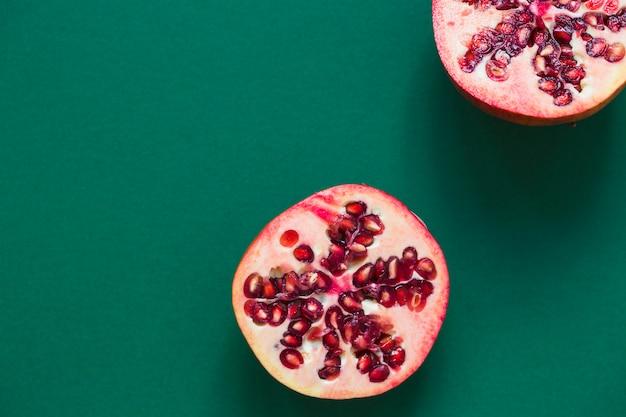 Halbierter granatapfel zwei auf grünem hintergrund