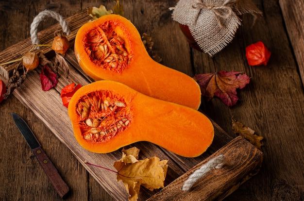 Halbierter orange kürbis auf rustikalem holztablett. gesunde ernährung und ländliches stillleben