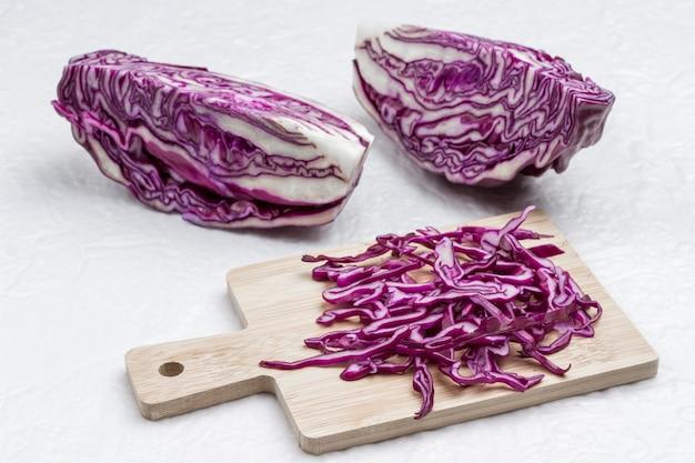 Halbierter rotkohl, geschnittener kohl auf schneidebrett. frisches veganes essen. weißer hintergrund.