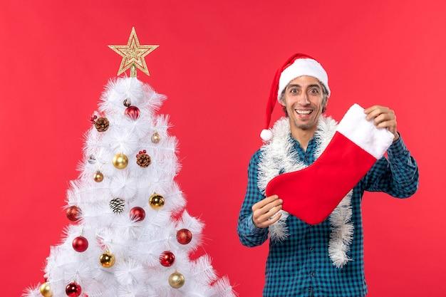 Halbkörperaufnahme des jungen mannes mit weihnachtsmannhut in einem blau gestreiften hemd und in der weihnachtssocke