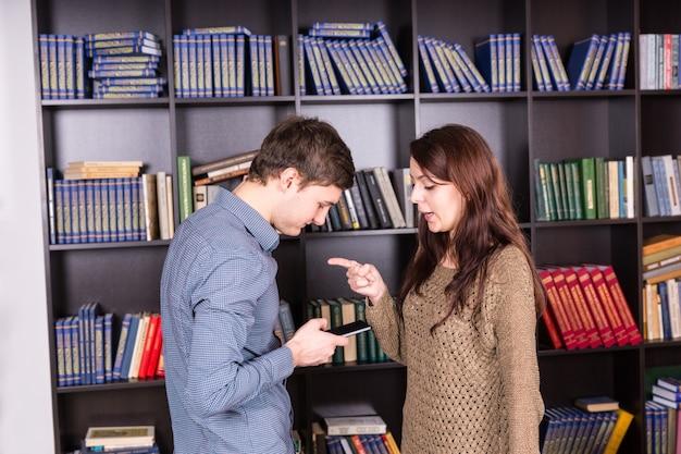 Halbkörperaufnahme einer jungen frau, die ihrem mann sagt, was er auf dem handy mitteilen soll, während sie in der bibliothek steht Premium Fotos