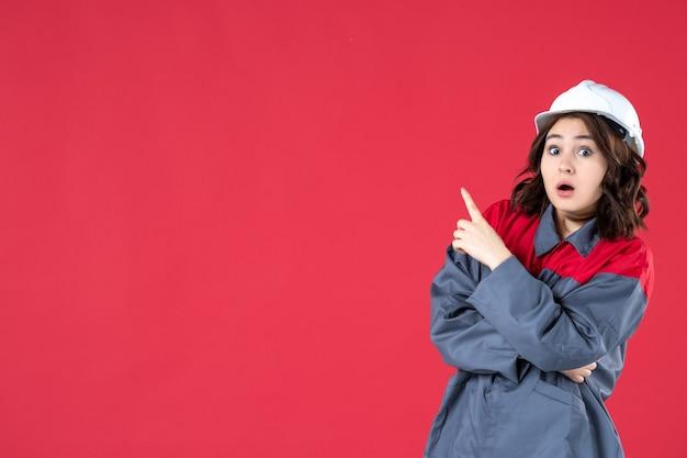 Halbkörperaufnahme einer schockierten baumeisterin in uniform mit schutzhelm und nach oben auf der rechten seite auf isoliertem rotem hintergrund