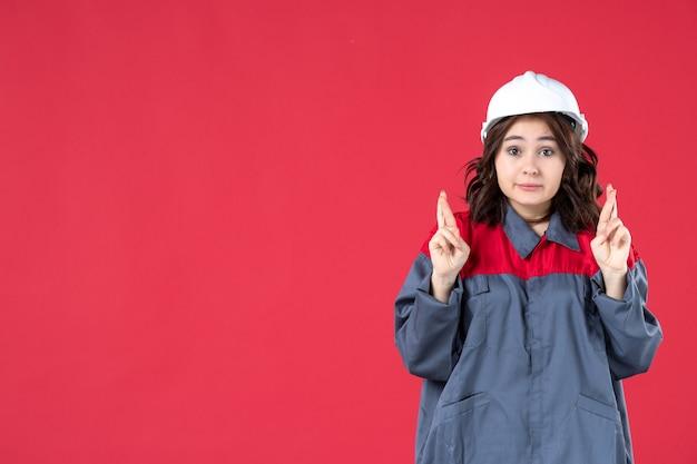 Halbkörperaufnahme einer unsicheren baumeisterin in uniform mit schutzhelm und überkreuzung der finger auf isoliertem rotem hintergrund