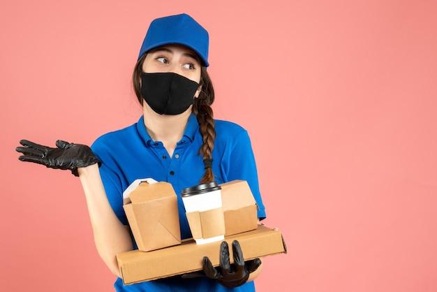 Halbkörperaufnahme eines denkenden kuriermädchens mit medizinischer maske und handschuhen, das bestellungen auf pastellfarbenem pfirsichhintergrund hält