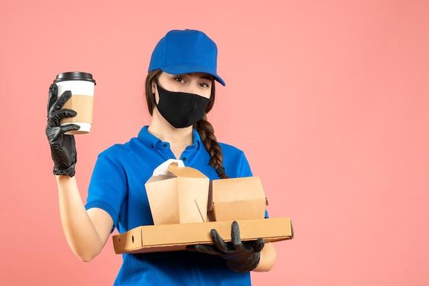 Halbkörperaufnahme eines fleißigen kuriermädchens mit medizinischer maske und handschuhen, das bestellungen auf pastellfarbenem pfirsichhintergrund hält holding