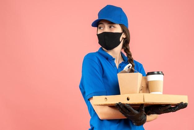 Halbkörperaufnahme eines fokussierten kuriermädchens mit medizinischer maske und handschuhen, das bestellungen auf pastellfarbenem pfirsichhintergrund hält holding